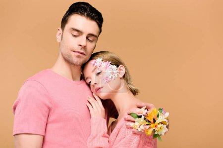 Foto de Mujer que a hombre hermoso con flores en mano aislado en beige - Imagen libre de derechos