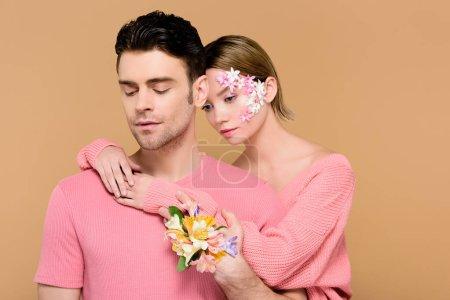 Foto de Atractiva novia con flores en la cara abrazando los hombre aislado en beige - Imagen libre de derechos
