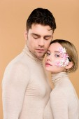 tender woman with flowers on face standing with handsome man isolated on beige