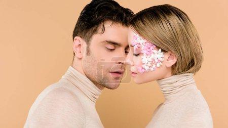 Foto de Hombre hermoso mirar novia guapa con los ojos cerrados aislados en beige - Imagen libre de derechos
