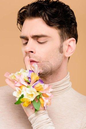 Foto de Hombre guapo con alstroemeria flores en mano mostrando hush signo aislado en beige - Imagen libre de derechos