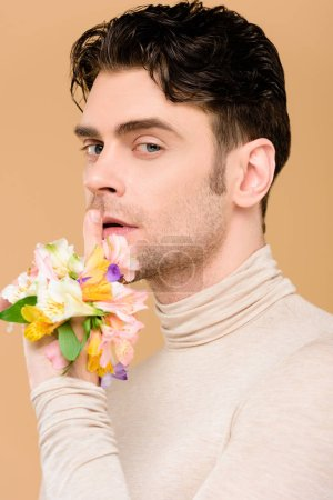 Foto de Hombre hermoso con flores en mano mostrando hush signo aislado en beige - Imagen libre de derechos