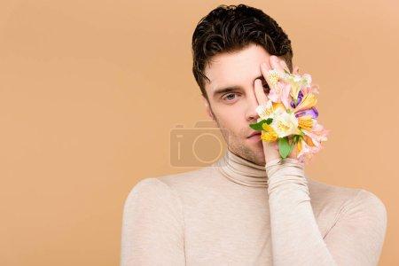 Foto de Hombre hermoso con flores en mano cubriendo un ojo aislado en beige - Imagen libre de derechos