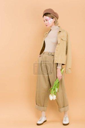 Photo pour Femme élégante en béret tenant le bouquet de fleurs isolées sur beige - image libre de droit