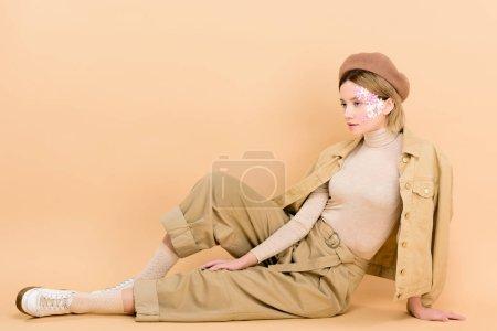 Foto de Chica elegante en beret posando mientras sentada en el piso aislado en beige - Imagen libre de derechos