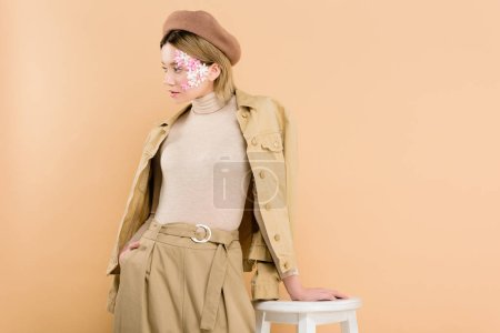 Photo for Stylish woman in beret standing near chair isolated on beige - Royalty Free Image