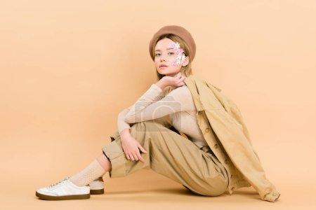 Photo pour Jolie fille en béret posant tout en étant assis sur le sol isolé sur beige - image libre de droit