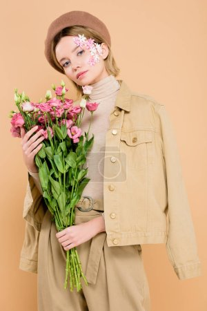 Photo for Trendy woman with flowers on face holding bouquet isolated on beige - Royalty Free Image