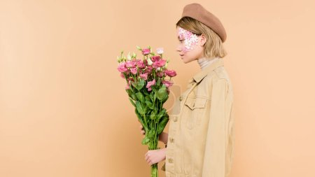 Photo for Side view of stylish woman with flowers on face holding bouquet isolated on beige - Royalty Free Image