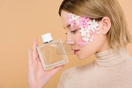 Foto de Mujer atractiva con flores en la cara mirando la botella de perfume aislado en beige - Imagen libre de derechos