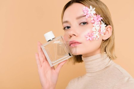 Photo for Beautiful woman with flowers on face holding bottle of perfume isolated on beige - Royalty Free Image