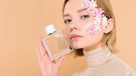 Foto de Seguros de mujer con flores en la cara sosteniendo la botella de perfume aislado en beige - Imagen libre de derechos