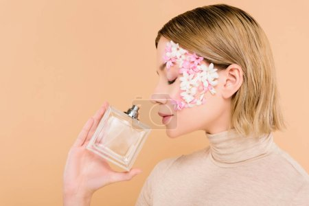 Photo for Beautiful woman with flowers on face smelling perfume isolated on beige - Royalty Free Image
