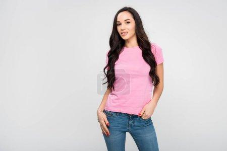 schönes Mädchen, das mit der Hand in der Tasche steht und isoliert auf grau lächelt