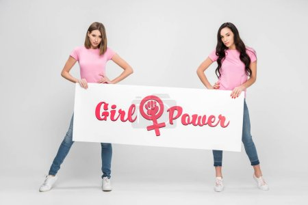 Photo for Beautiful girls holding large sign with girl power lettering on grey background - Royalty Free Image