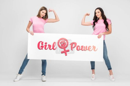 Foto de Attractive women showing muscles and holding large sign with girl power lettering on grey background - Imagen libre de derechos