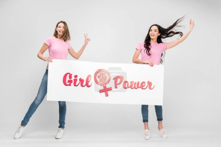 Photo pour Cheerful women holding large sign with girl power lettering on grey background - image libre de droit