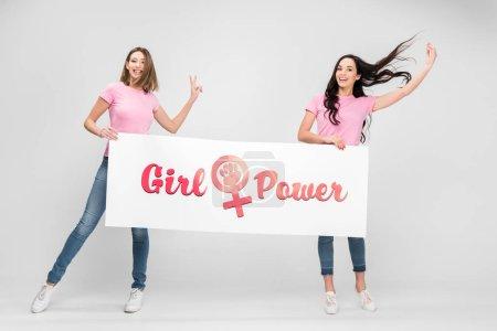 Foto de Cheerful women holding large sign with girl power lettering on grey background - Imagen libre de derechos