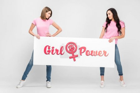 Foto de Attractive women looking at each other and and holding large sign with girl power lettering on grey background - Imagen libre de derechos