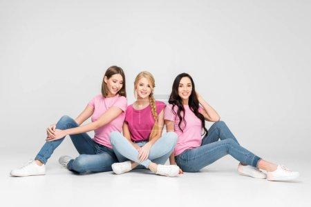 Foto de Cheerful girls sitting with crossed legs on floor on grey background - Imagen libre de derechos