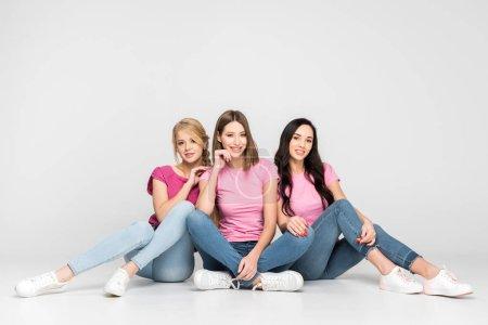 Foto de Cheerful girls sitting near friend with crossed legs on floor on grey background - Imagen libre de derechos