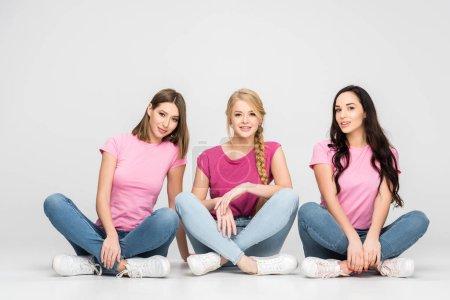Foto de Happy girls sitting with crossed legs on floor on grey background - Imagen libre de derechos