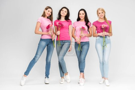 Photo for Attractive girls standing with flowers and smiling on grey background - Royalty Free Image