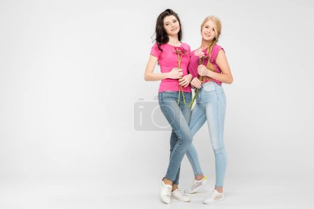 Photo for Beautiful women holding flowers and standing on grey background - Royalty Free Image