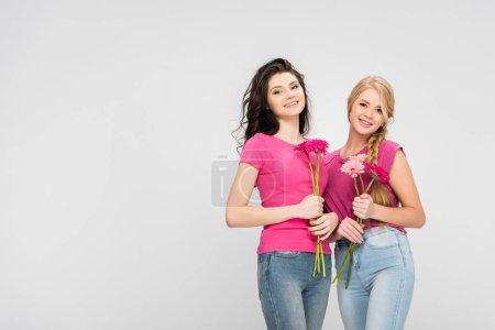 Foto de Happy women holding flowers and standing isolated on grey - Imagen libre de derechos