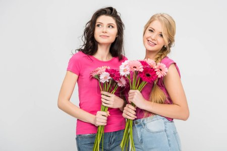 Photo for Happy girls holding flowers and standing isolated on grey - Royalty Free Image