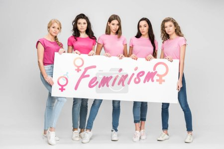 Photo pour Attractive girls holding large sign with feminism lettering on grey background - image libre de droit