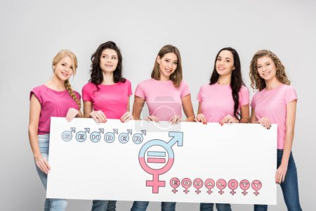 Photo for Beautiful young women holding large sign with gender equality symbol isolated on grey - Royalty Free Image