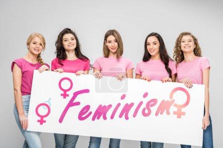 Foto de Cheerful girls holding large sign with feminism lettering isolated on grey - Imagen libre de derechos