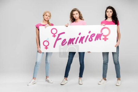 Foto de Confident girls holding large sign with feminism lettering on grey background - Imagen libre de derechos