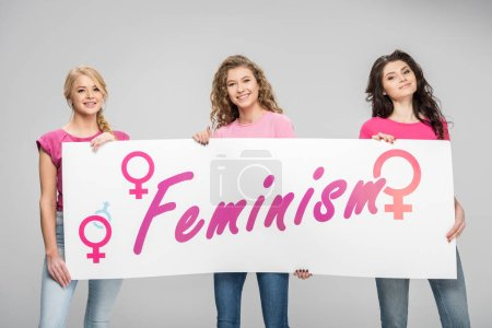Foto de Happy girls holding large sign with feminism lettering isolated on grey - Imagen libre de derechos