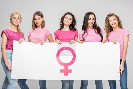 Photo pour Femmes heureux holding grande pancarte avec symbol féminin isolé sur fond gris - image libre de droit