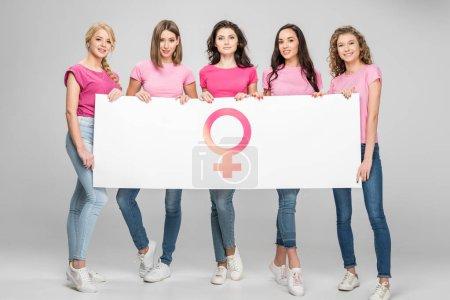 Photo pour Jolies filles tenant le grand panneau avec le symbole féminin sur fond gris - image libre de droit