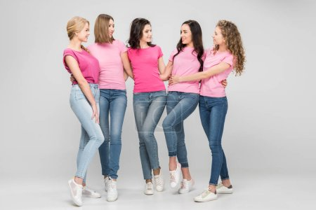 Photo for Cheerful young women standing and looking at each other on grey background - Royalty Free Image