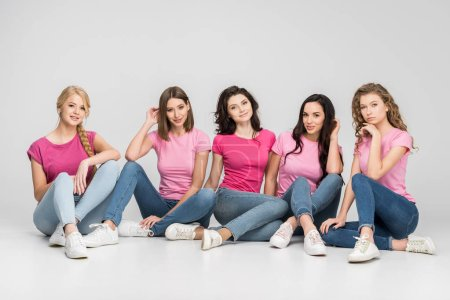Photo for Happy young women sitting on floor and smiling on grey background - Royalty Free Image