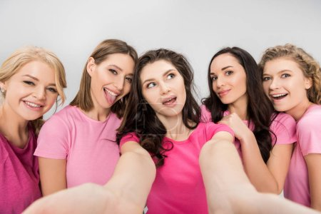 Foto de Funny young women taking selfie and smiling isolated on grey - Imagen libre de derechos