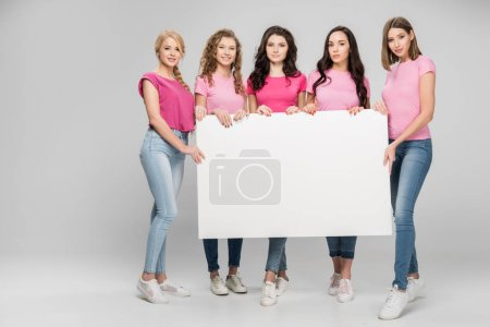 Photo for Cheerful girls standing with empty board on grey background - Royalty Free Image