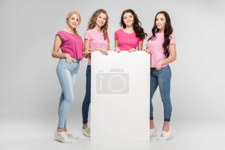 Photo for Happy girls holding empty board and smiling on grey background - Royalty Free Image