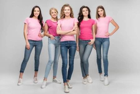 Photo for Cheerful girl standing with crossed arms near beautiful women on grey background - Royalty Free Image