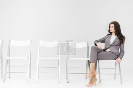 Photo for Serious woman sitting with crossed legs on chair isolated on grey - Royalty Free Image
