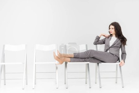 Photo for Serious woman putting legs on chair while sitting isolated on grey - Royalty Free Image