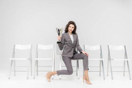 Photo pour Femme réussie tenant trophée alors qu'elle était assise sur une chaise isolée sur gris - image libre de droit