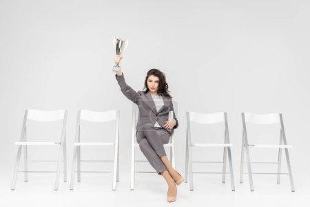 Photo pour Femme réussie tenant trophée au-dessus de la tête tout en étant assis sur une chaise isolée sur gris - image libre de droit