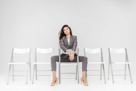beautiful woman sitting on white chair isolated on grey