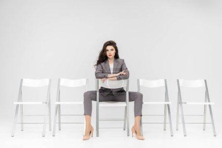 ernste schöne Frau sitzt auf weißem Stuhl isoliert auf grau