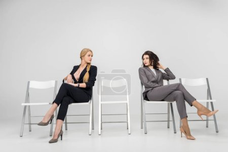 businesswomen sitting with crossed legs and looking at each other isolated on grey